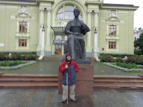 Tony in front of a bronze statue of Olha Kobylianska in Theatre Square with the theatre immediately behind. Olha Kobylianska (1863-1942) was a modernist writer and feminist. The theatre was named after her in 1954, while the statue was placed in front in 1980.