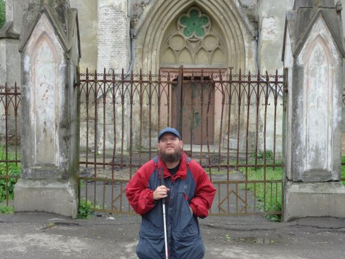 Tony outside the entrance to the Church of the Sacred Heart of Jesus. Rusted iron gates with the main doorway beyond.