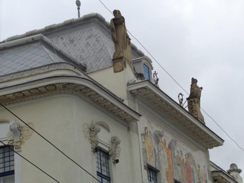 A closer view of the statues on the roof of the Chernivtsi Art Museum building.