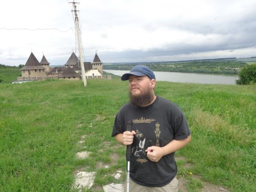 Tony standing in a field with the towers and walls of Khotyn Fortress rising up behind. The Dniester River can be seen below.