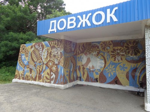 An old Soviet-era bus shelter decorated with a mosaic pattern depicting plants and flowers.