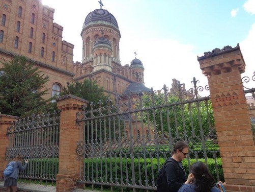 Wall and railings outside Chernivtsi National University (Yuriy Fedkovych Chernivtsi National University). The dome of the Church of Three Saints, part of the Seminary Building, can be seen behind.