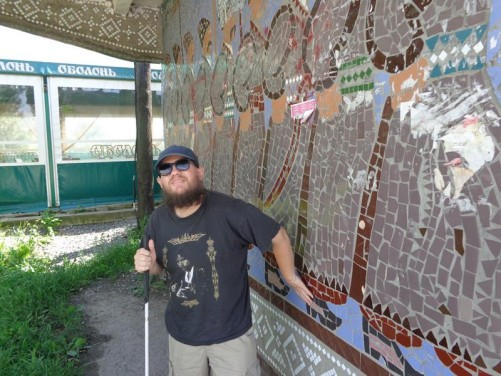 Tony by another Soviet-era bus shelter. It's decorated with a mosaic depicting a historic scene featuring a line of soldiers.
