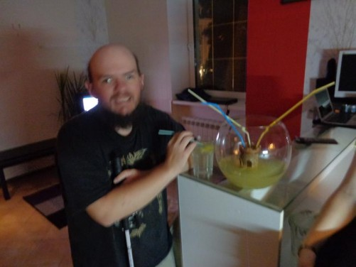 Tony at the hostel having a drink. On the table is a 'fish bowl' with straws for drinking the vodka inside!