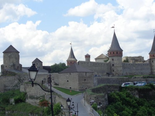 View along a road leading to Kamianets-Podilskyi Castle. In front are the castle's substantial stone outer walls with several round towers with pointed roofs.