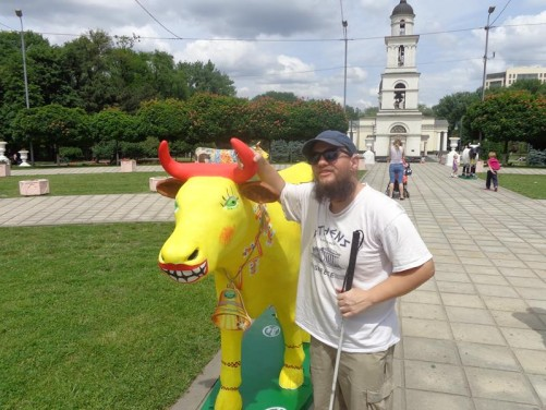 Tony touching a life-sized bright yellow plastic cow in Cathedral Park.