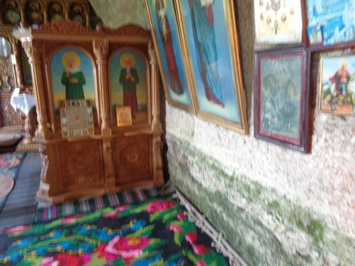 A chapel inside the Cave Monastery. Colourful religious icons hanging on the walls.