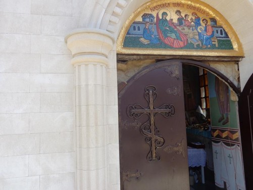 A metal door into the church. A cross on the front.