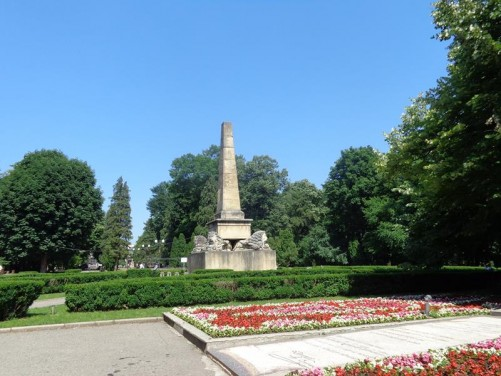 Another view of the Obelisk of Lions surrounded by flower beds and ornamental hedges.