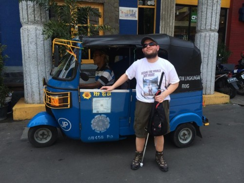 Tony in front of a bajaj. These three-wheeled vehicles are used as taxis to transport people around the city.