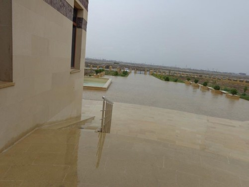 Outside Gobustan Museum in the rain. In the distance a barren semi-desert wasteland can just be discerned. This area includes white salt flats and natural oil pools seeping up to the surface.