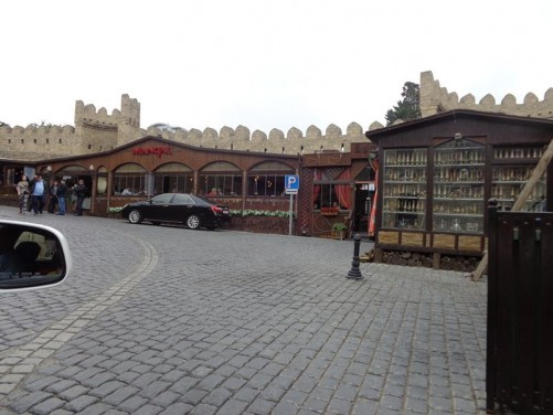 Inside the Old City. The stone city walls can be seen in front with battlements along the top. The walls date back to at least the 12th century. Below the walls, a shop and restaurant built of wood in traditional style.
