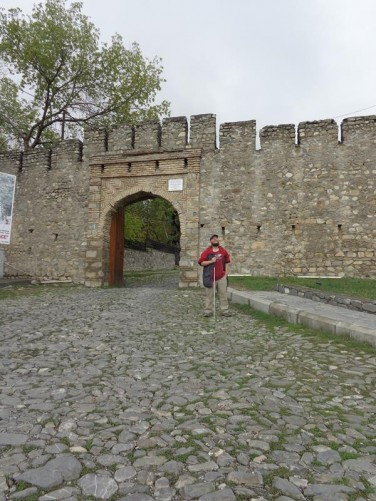 Tony leaving the fortress. A cobblestone road with a gate through the fortress walls behind.