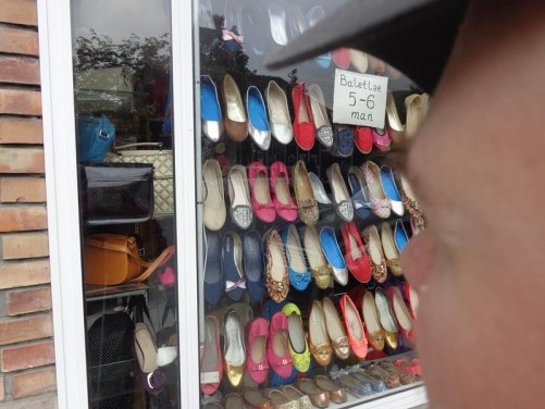 Window display of a ladies' shoe shop. Rows of brightly coloured shoes.