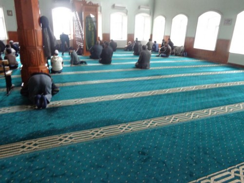 Inside the mosque. Men kneeling in prayer.