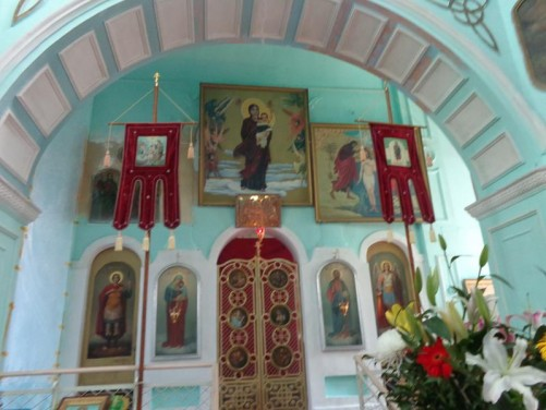 In front of the main altar inside the Alexander Nevsky Church. This includes a number of religious icons on a turquoise coloured wall.