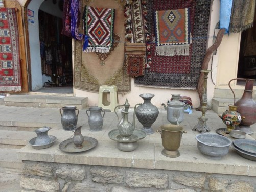 Outside a souvenir shop selling various metal plates, bowls, jugs and other vessels, as well as rugs.