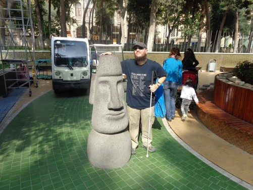 Tony with his hand on a stylised stone head, again in Fountain Square.