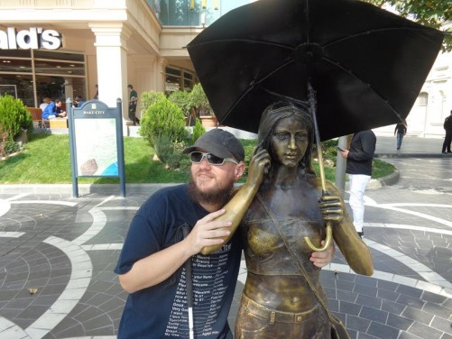 Tony posing with another sexy bronze lady. She is holding an umbrella and mobile phone.