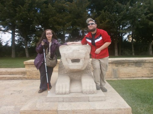 Tatiana and Tony either side of a stone lion. This is one of twelve pairs of lions that line the Road of Lions, a 262-metre long pedestrian walkway leading to the Ceremonial Plaza and mausoleum. The lions are carved in a similar style to Hittite archaeological finds.