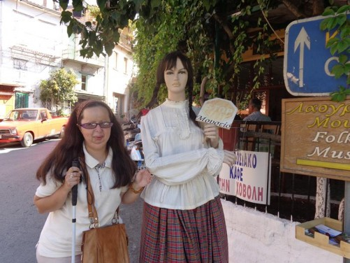 Tatiana next to a female manikin in traditional dress outside a restaurant.