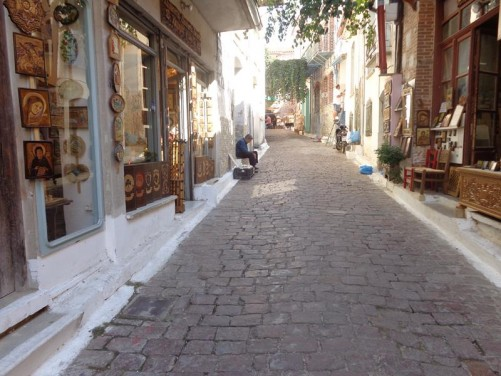 Looking up a narrow street. Shops selling various craft items, including religious icons.
