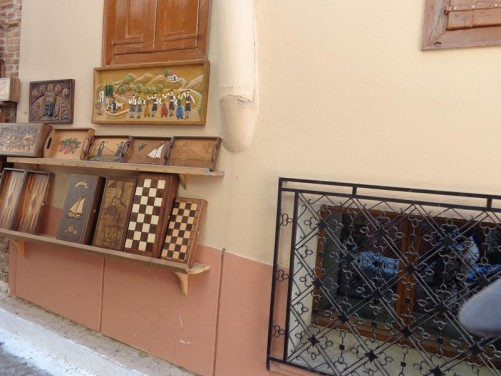 Wooden craft items for sale outside a shop, including chess boards and trays with inlaid decoration.