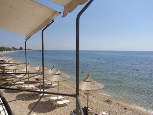 View along the narrow sandy beach. Line of sun umbrellas and loungers.