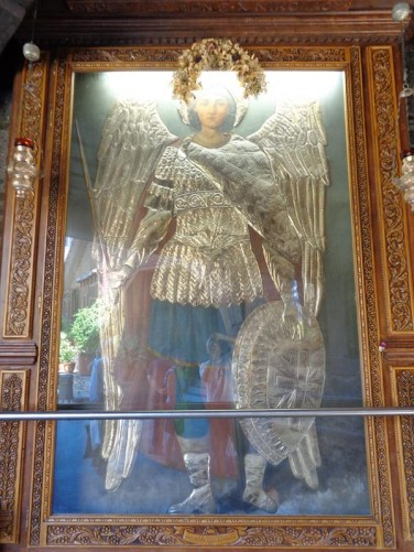 A life-sized icon of Archangel Michael in full regalia hanging on a wall inside the church. This is different from the famous icon described above.