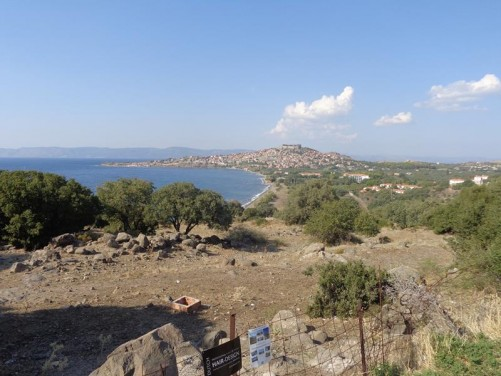 On a hill, looking north across a bay with Mithymna town at the far side. Mithymna's large Byzantine castle can just be seen on top of the hill with the town spread out below.