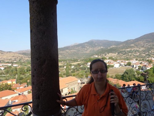 Tatiana by a stone column outside the church. View of the town and the surrounding hills and fields in the background.