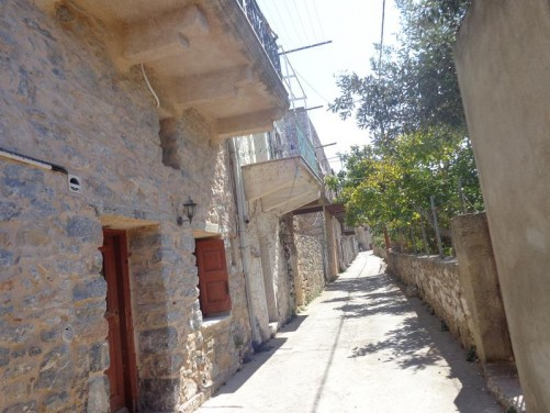 A straight narrow street in Mesta village. Small stone-built houses along the left side. The houses in the village were deliberately built tightly side-by-side creating protective walls around the perimeter to protect against pirate raids.