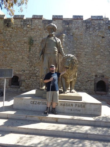 Tony in front of the Cezayirli Gazi Hasan Pasha statue, touching the lion. In the background, the large stone outer wall of Çesme Castle.