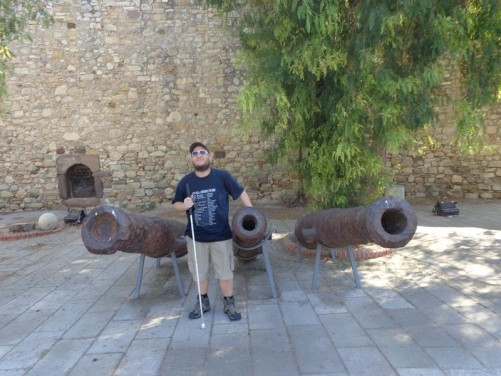Tony touching one of three rusty canons. The walls of Çesme Castle again behind. The castle dates from the early 16th century. Its walls dominate the town.
