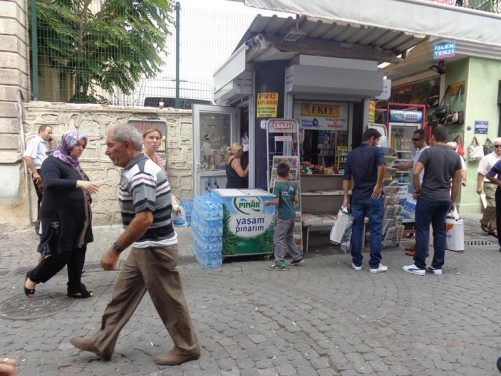 A street in the shopping market area. People at a typical kiosk selling newspapers, drinks and confectionery.