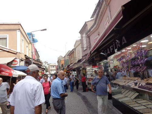 Crowded street lined with shops. A large jewellery shop on the right side.