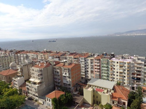 Looking down at apartment buildings along the sea front and the sea beyond.
