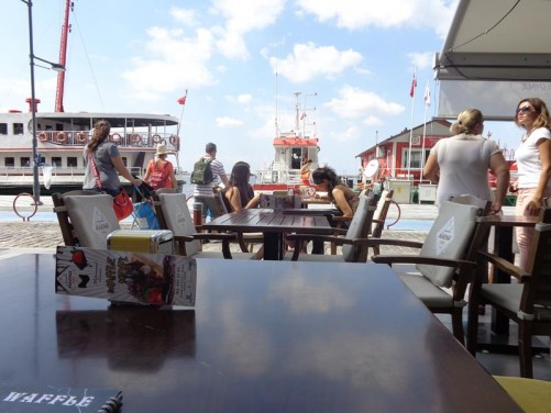At a café table by the sea front promenade. Boats moored in front.