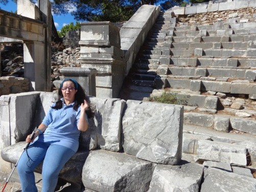 Tatiana sitting on a stone seat at the theatre.