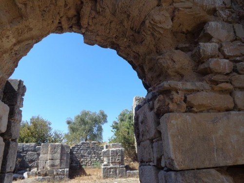 Looking through a stone archway into the remains of a room. Faustina Baths.