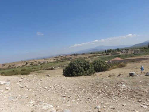 View of the surrounding landscape - parched fields and rolling hills. Other archaeological remains just visible in the middle distance. Higher hills and mountains in the far distance.