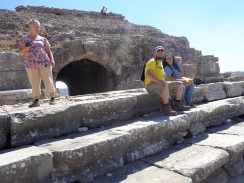 Tony and Tatiana sitting on stone seats within the theatre. The theatre was first built in the 4th century BC by the Greeks. Later re-constructed by the Romans. It once had capacity for 15,000 spectators.