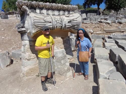 Tony and Tatiana by a decoratively carved stone block, possibly at column base, at Didyma.