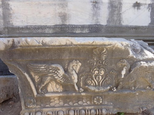 A carved stone block with two griffins depicted on the side.