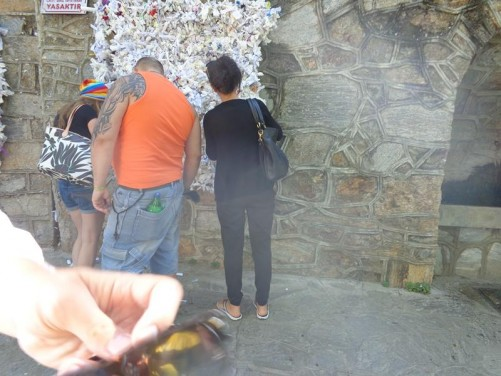 Visitors adding messages to a prayer wall near the House of the Virgin Mary. Thousands of messages are already attached on small pieces of paper or fabric.