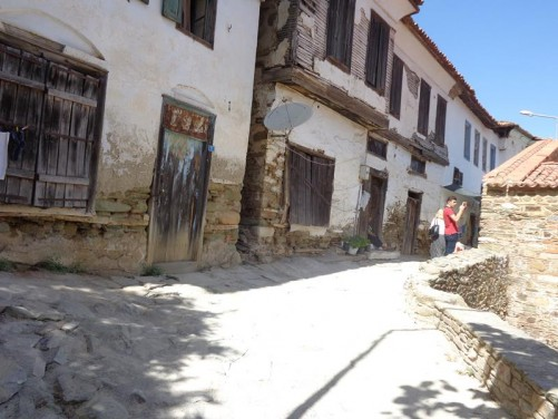 A narrow street with a row of traditional houses. Sirince was settled when Ephesus was abandoned in the 15th Century, however, much of what is seen today dates from the 19th century.