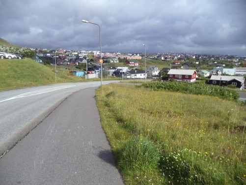 Heading down a road. Buildings on the edge of Tórshavn spread out over the grassy terrain.