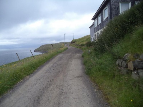 Heading up a narrow unsurfaced road on Nólsoy. A couple of houses sitting on the exposed grass covered slope.