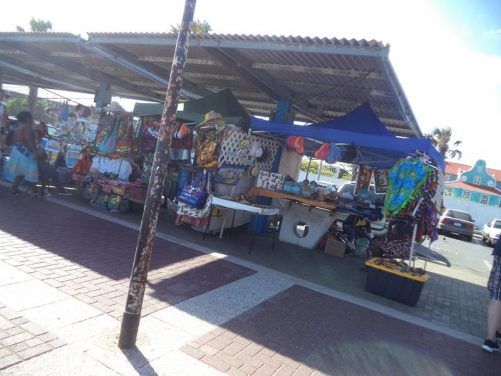 A market stall at the waterfront selling colourful bags amongst other items.