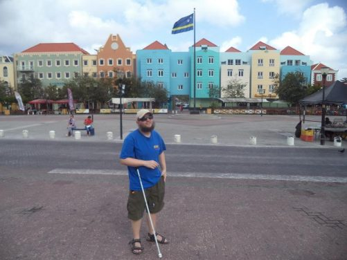 Tony in Plaza Brión. In view the flag of Curaçao flying from a tall pole and colourfully painted buildings at the edge of the square.